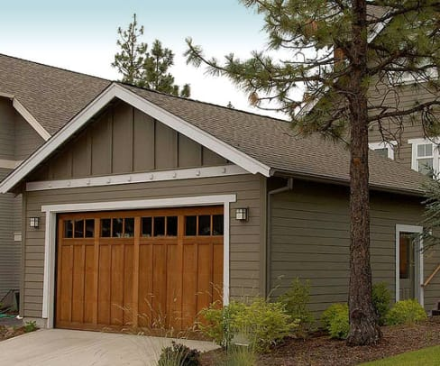 For a bungalow on a corner lot, The Bungalow Company designed an unobtrusive garage with alley access, separated by a dog-run and a patio from the main house.