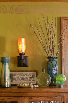 Art pottery and glass lit by a sconce with Lundberg glass in a dining-room vignette.