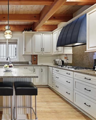 An understated blackened steel hood by Raw Urth complements a handsome kitchen with Prairie details.
