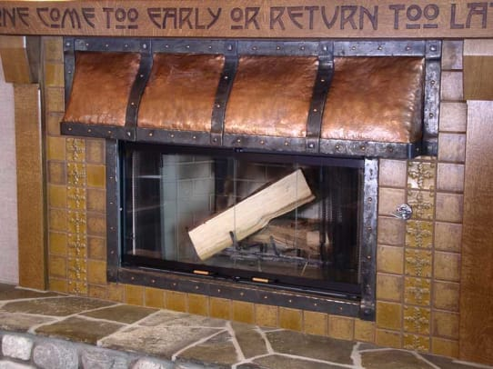 The motto is in the lintel over a fireplace capped by a copper hood with heavy strapping, by Joseph Mross of Archive Designs.