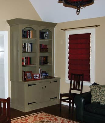 With a quiet coat of paint in a period color, and reproduction hardware, the cabinets were made to blend with the room.