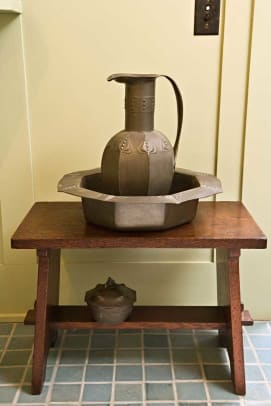 The Osiris Pewter jug by George Logan sits n a 1902 Gustav Stickley bench.