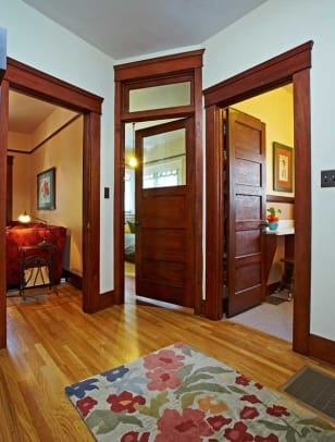 Opening to the hall are a reading room, sunroom/guest room with a transom, and the bath.