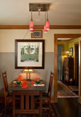 """""""The Stag,"""" a period design by C.F.A. Voysey produced by J.R. Burrows, is framed in the breakfast room. This table is an antique Stickley Bros. piece."""