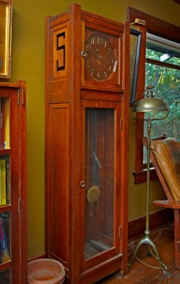 The homeowner counts his Stickley 'S' grandfather clock among his favorite furnishings. To its right stand a Tiffany Harp lamp and one of two #369 Stickley Morris chairs.