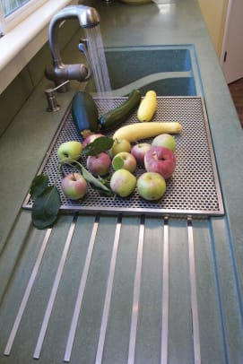 Embedded metal strips encourage drainage in a concrete sink with an S-shaped divider, from Sonoma Cast Stone.