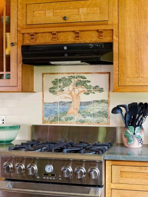 The centerpiece of the new kitchen is a large gas stove set into the quarter-sawn oak cabinets and topped by a vent hood.