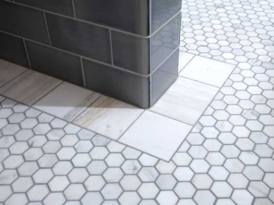 Hexagonal floor tiles and the unusual hand-cut border are marble.