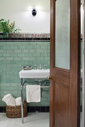 "In the guest bath, green 3"" x 6"" subway tiles and a reproduction Kohler 'Memoir' pedestal sink have a vintage look."
