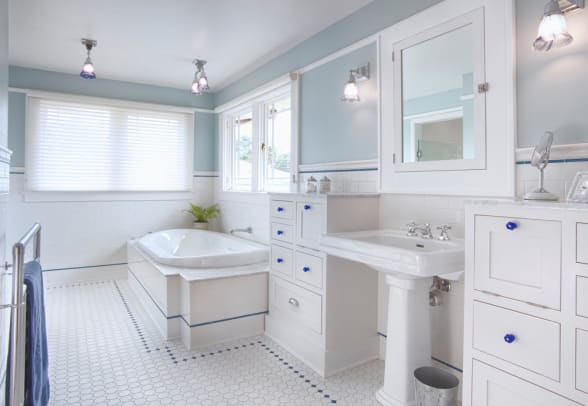 The master bath has plenty of storage in cabinets inspired by 1920s millwork.