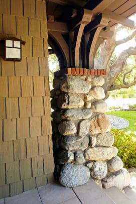 The porch ceiling is held on battered stone piers that support wood brackets in a Japanesque arrangement.