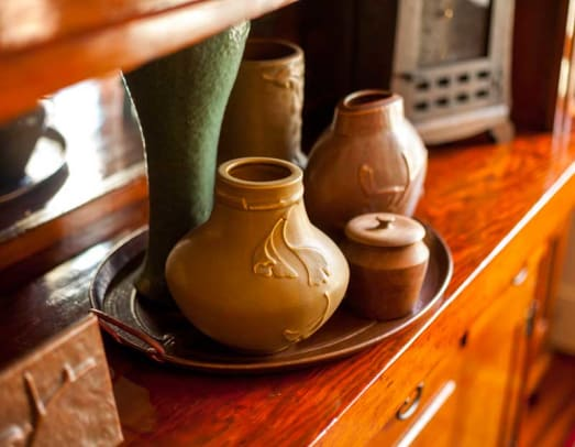 The couple's collection of sought-after LoneSomeVille Pottery includes blue-green bowls and an assortment of vases; the lidded jar is wood, from Belize.