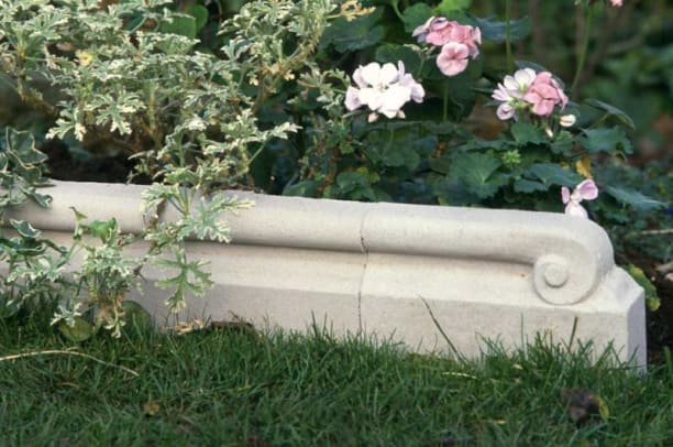 Scrolled lawn edging is cultured stone, by Tradewinds.