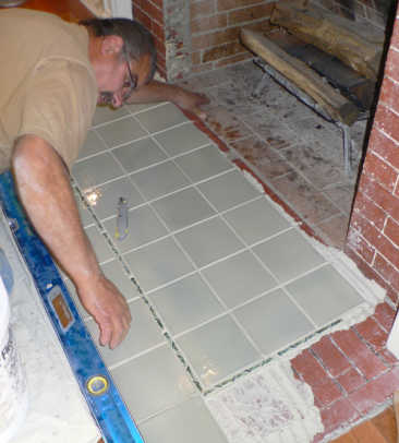 Bill uses a level and his eyes to make sure tiles line up before the mortar is fully set.
