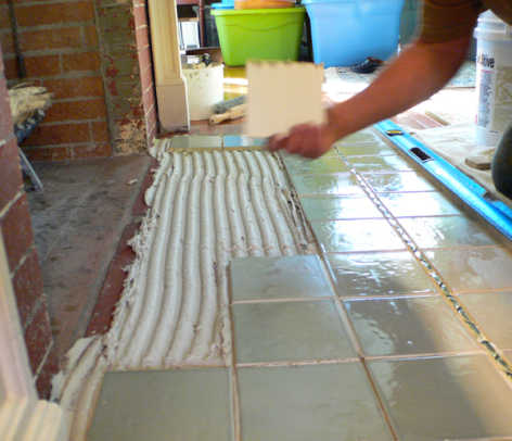 He lays tile quickly once the mortar is spread, continually checking for lippage, a difference in height from one tile to the next.