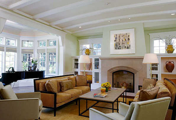 Paneled wainscot continues into the living room with its elegantly curved ceiling. The fireplace flanked by bookcases and high windows is characteristic of many Arts & Crafts houses.