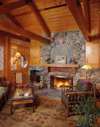 This rustic stone fireplace wall and mantel with hand carving is in a new house.