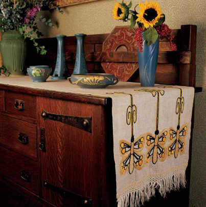 A Stickley Brothers sideboard in the dining room holds a collection of Roseville, Van Briggle, and Rookwood pottery, all set on an antique runner embroidered with stylized dragonflies.