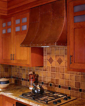 A modern cooktop blends in when accompanied by period cabinets, art tile, and a copper hood. Photo by David Duncan Livingston.