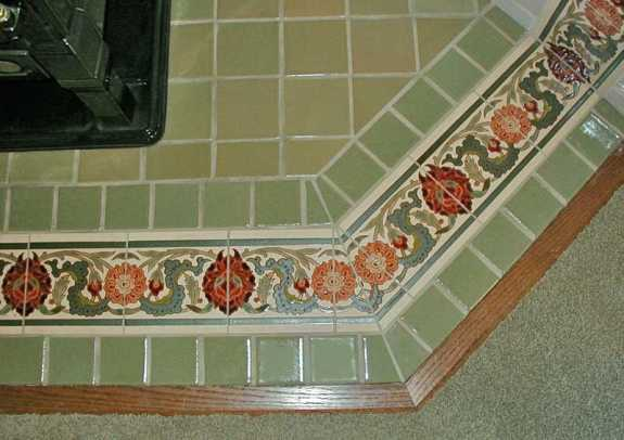 An inlaid border of Hispano–Moresque tiles from Designs in Tile on a freestanding fireplace pad.