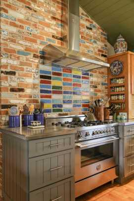 Reclaimed garden bricks were used on one wall of the kitchen (originally an attached garage). Colorful paint creates a focal point behind the stove.