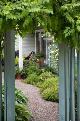 Glimpse of addition and side porch through the gate laden with trumpet vine.