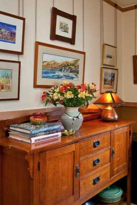 Watercolors painted by owner Steve Dowty hang above an oak Craftsman-style cabinet used for  extra kitchen storage in the breakfast room.