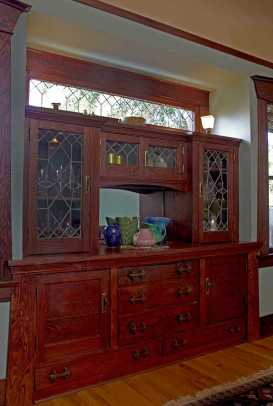 In the dining room, the built-in buffet has leaded-glass doors and rugged wood pulls.