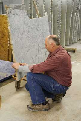 "Longtime employee Doug Teter marks a slab to be cut. It's similar to laying out a dress pattern on fabric, he says: ""every day it's a different puzzle."""