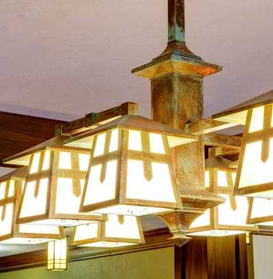 Reproduction lighting has a patinated finish.