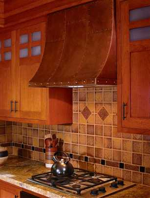 Ceramic tiles in the backsplash are enlivened by tumbled stone and bronze liner tiles. A copper hood is warm and practical.