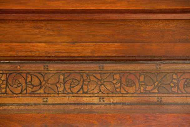 In the great room, this original paper border survives in the crown moulding beneath the soaring ceiling.