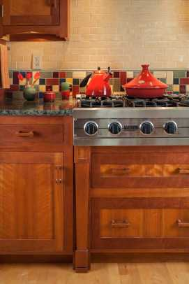 A tired, remodeled kitchen was gutted and rebuilt with cherry cabinets and stained-glass transoms by local artisans.