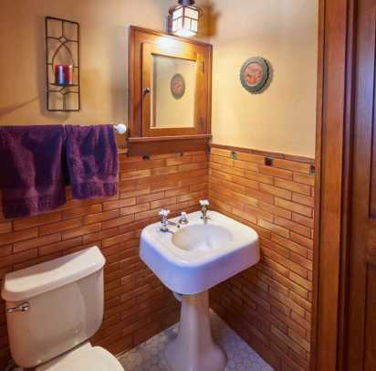 The upstairs powder room has a salvaged 1920 sink, original medicine cabinet, and tile from Clay Squared.