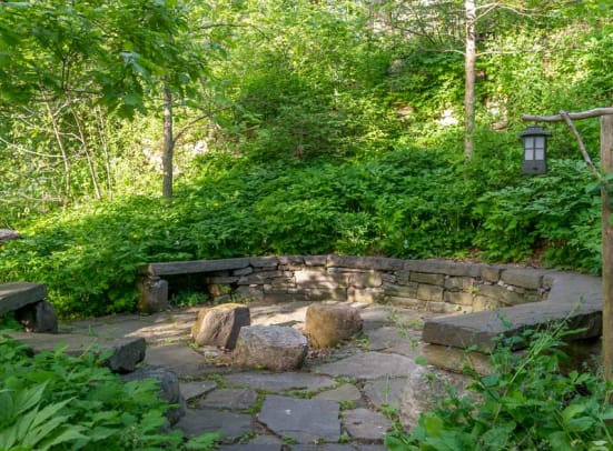 """The """"council ring"""" made up of salvaged New York City curbing allows the family to gather around a firepit."""