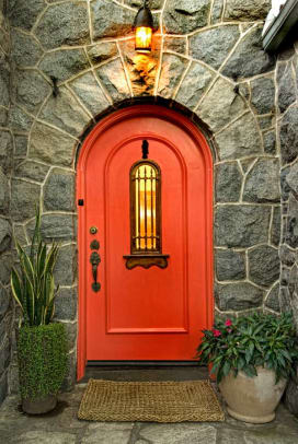 The Mediterranean-style front door is painted in a Southwest red.