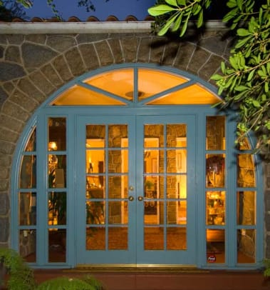 A view to the open interior is through French doors set in a stone arch.