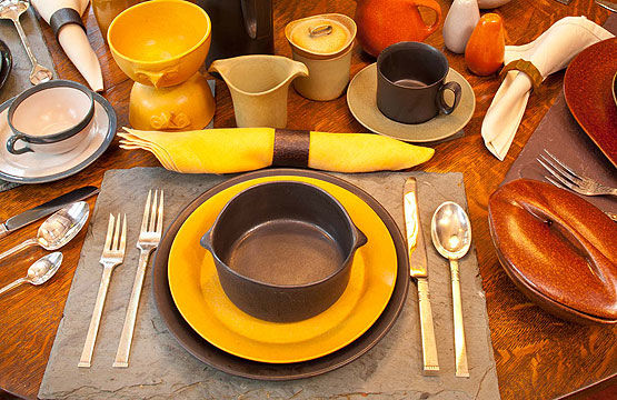An Arts & Crafts house sets an eclectic table, mixing in dinnerware from later eras. Common elements are matte glazes and earthy colors. Russel Wright dinnerware is flanked by Community Silver flatware in the 1948 pattern 'Morningstar'. The teapot is a contemporary Swedish piece. The tall 1960s coffeepot is from Bennington Pottery. The small cup and saucer are unmarked A&C-era pieces. Photo by Bruce Martin.