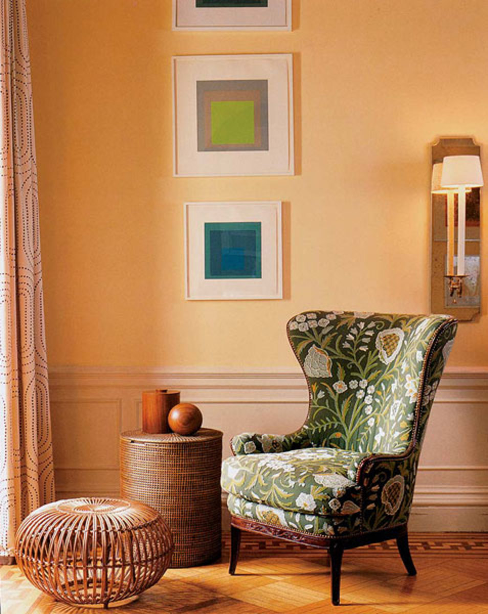Modern geometric prints are juxtaposed with a traditional wing chair covered in crewel.