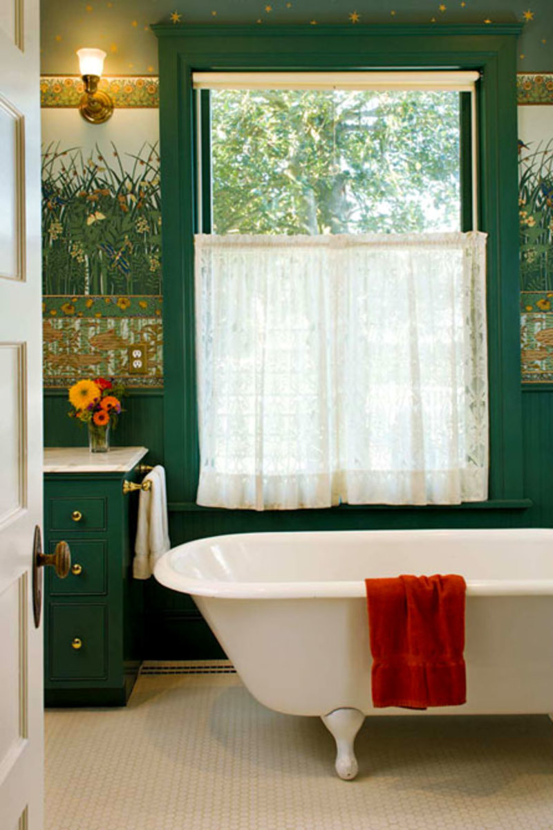A clawfoot tub and multi-part wall treatment over a wood wainscot are suitable for the 1901 transitional house. Hex-tile floor and roller shade with lace curtain complete the coherent look. Photo by William Wright.