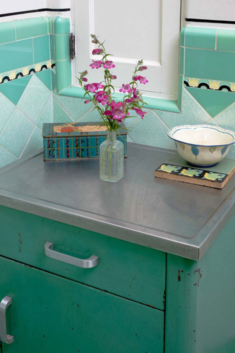 "The tile design and bullnose trim are obvious in this corner, where a ""shortcut"" door opens into the hallway linen closet. The green metal cabinet, likely from a medical or dental office, was a flea-market find."