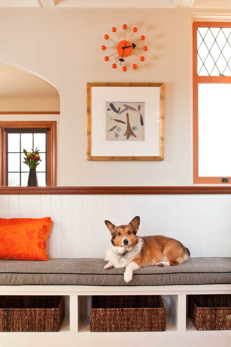 Yoda, the couple's Pembroke Welsh Corgi, relaxes on the built-in settle that divides kitchen from dining room.