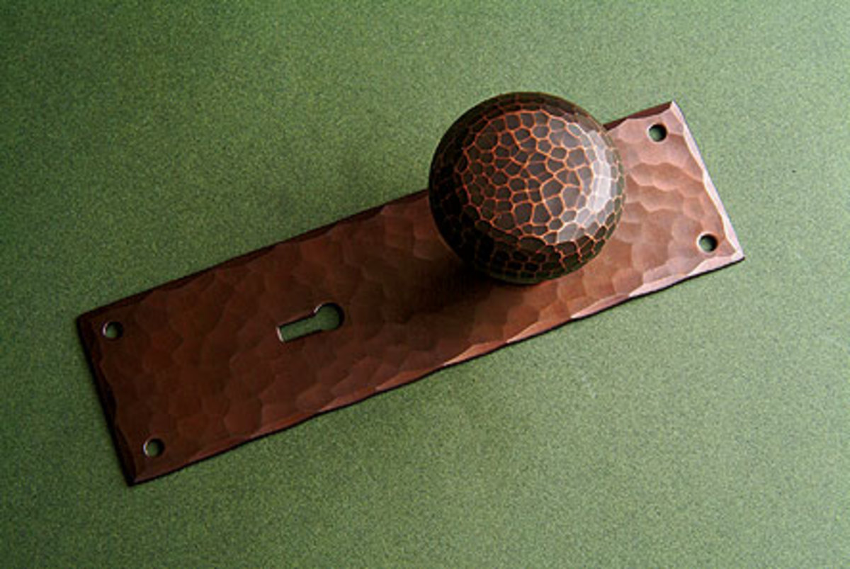 Plain-hammered knob and escutcheon #900U in antique copper from Crown City Hardware.
