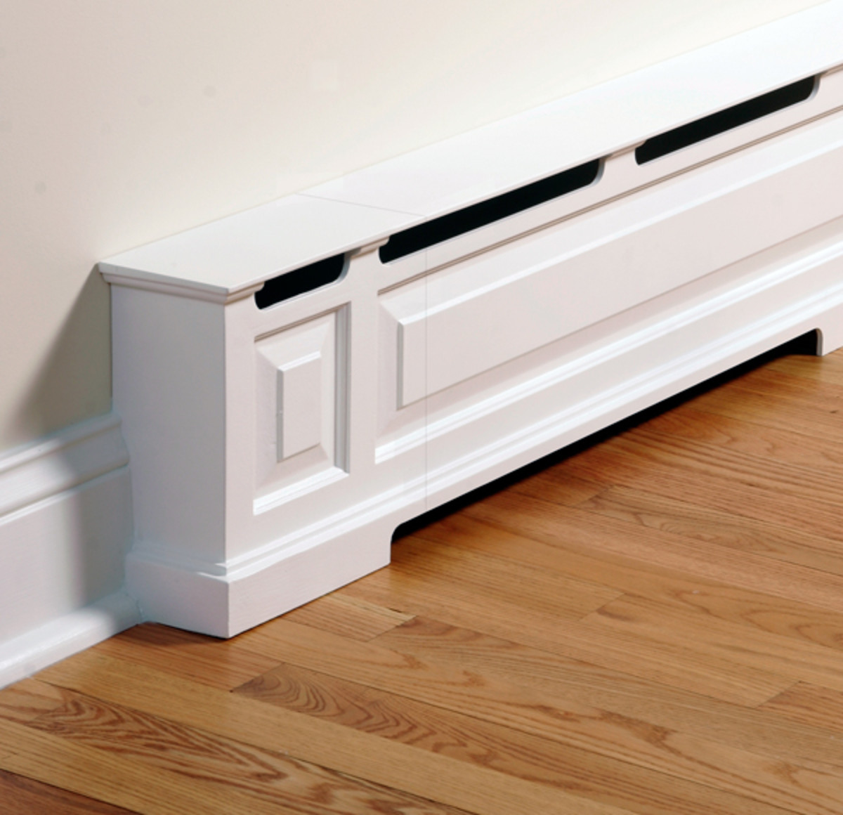 A baseboard heater is turned into room trim with a cover by OverBoards.