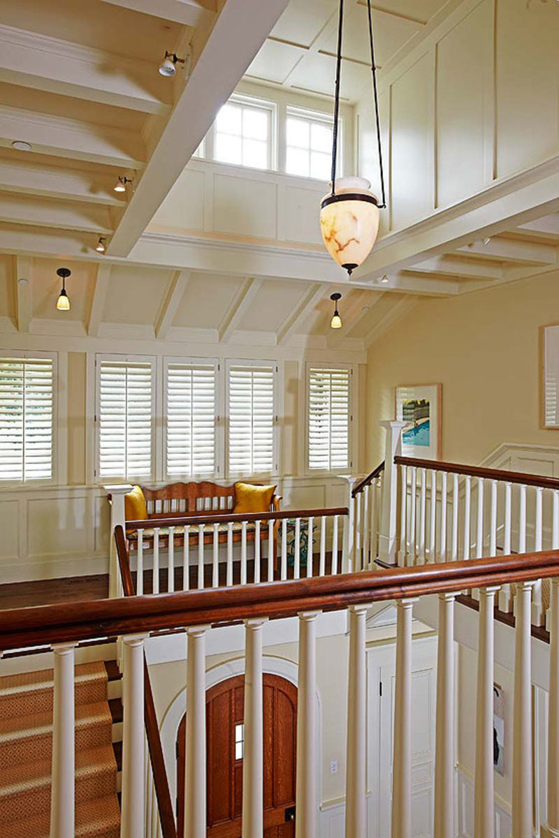 Beams, wainscot, and grouped windows lend scale to the dramatic entry hall rising three stories and flooded with light.