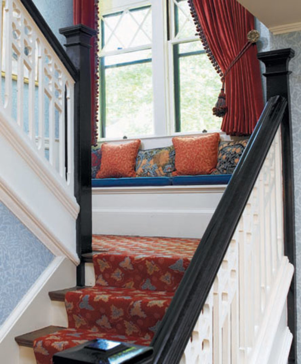 Tapestry pillows in William Morris designs accent a landing window seat in a Colonial Revival home. Photo by Greg Premru.