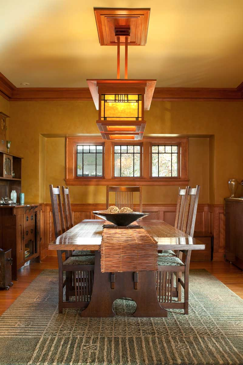 A custom chandelier illuminates the reproduction Stickley oak furniture in the dining room. Venetian plaster walls were finished in a warm, autumnal gold.  All photos by William Wright