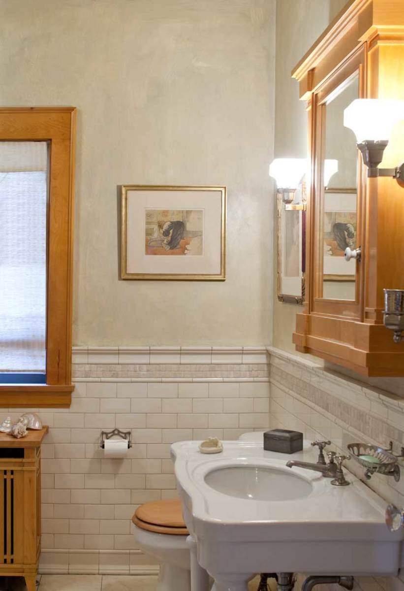 Period reproduction fixtures and subway tile made over the upstairs bath.