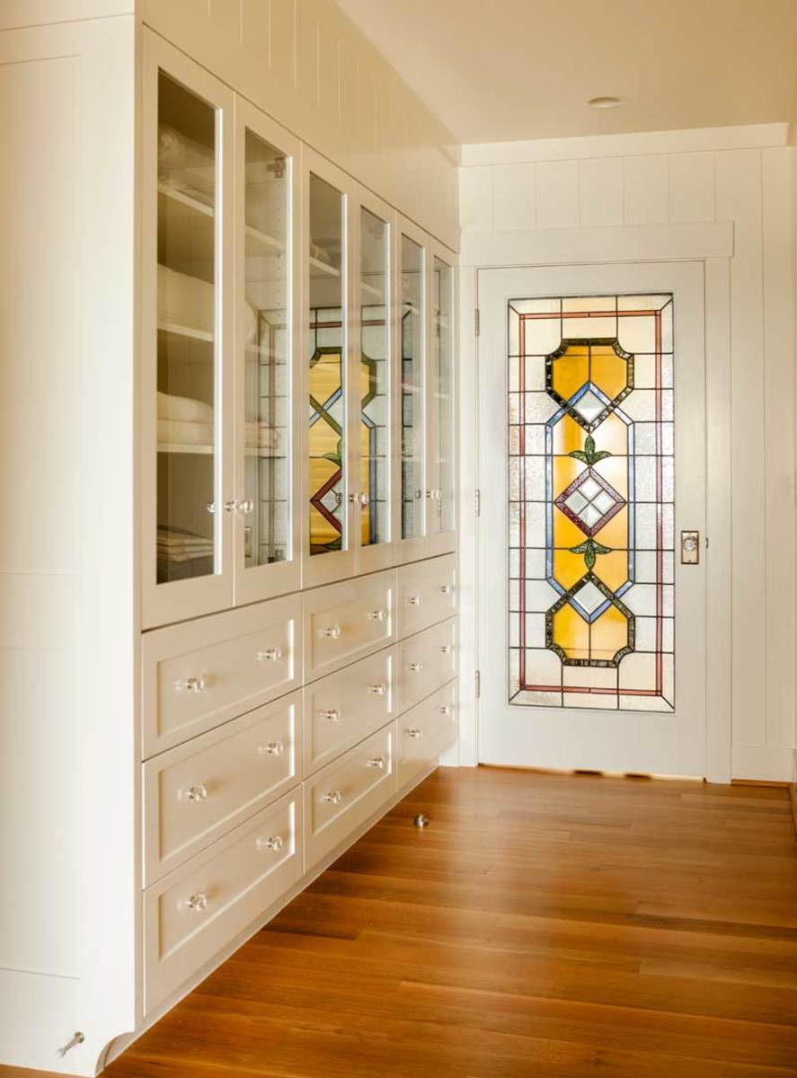 Early plans called for solid doors in the bank of linen cabinets; Overbay suggested glass above and drawers below for greater interest and better storage. New art glass adds beauty and provides privacy for the hobby room beyond.