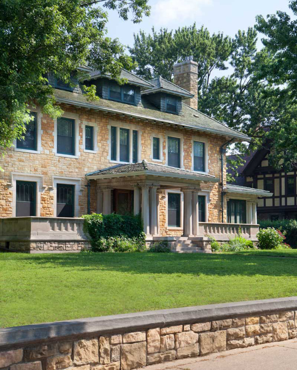 The facing of the foursquare house is Mankato stone. Carved eave brackets and column capitals, and Gothic hood moulds on first-floor windows, enliven the order of a house's symmetrical arrangement.